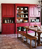 Country-house style kitchen-dining room with heavy wooden table and benches below wrought iron chandelier; matt red kitchen dresser in background