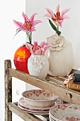 Pink lilies in white china vases and red glass vase next to traditional dinner service on vintage wooden shelving