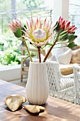 Tropical plants in white china vase with fluted surface and heart-shaped stones on wooden table