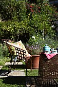 Sonniger Gartenplatz mit Gartenmöbeln aus Metall und Boden im Schachbrettmuster; auf dem Tisch Teekanne und Teetassen