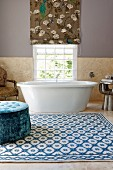 Spacious bathroom with blue velvet pouffe on patterned rug in front of bathtub below window