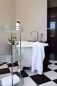 Free-standing, metal shelving unit and vintage bathtub on chequered floor in corner of bathroom