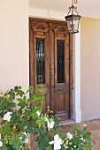 Rose bush and lantern outside antique, Indian front door with glass panels and metal grille