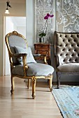 Gilt, Rococo armchair with pale blue velvet upholstery in front of small antique cabinet