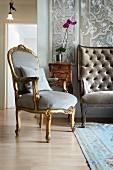 Goldener Rokoko Sessel mit hellgrauem Samtbezug vor antikem Schränkchen