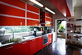 Fitted kitchen with red units and metal shelving next to open terrace door
