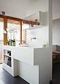 White partition element with sink, surface and shelves in front of glass wall with wooden louver blinds
