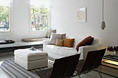 Bright living room with long bench below window, comfortable couch and black chairs