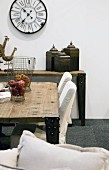 Rustic table and chairs with white loose covers; antique station clock on wall
