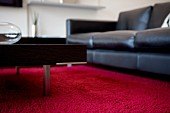 Black leather couch and coffee table with metal legs on red carpet