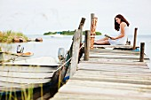 Woman sitting on jetty, reading book