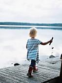 Kleines Mädchen mit Fischernetz auf einem Steg laufend