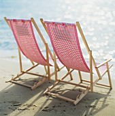 Two sun chairs on a sandy beach.