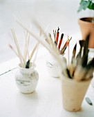 Pens and paintbrushes in jars.