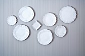 Collection of white china plates on wall