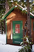 Mountain hut in snow with snow shoes & paddles hanging either side of door