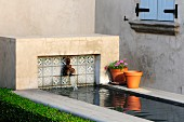 Stream with concrete surround and antique water spout next to grey house facade in sunshine