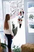 Girl standing in doorway receiving guests arriving on foot through snowy landscape