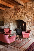 Room with stone walls, beam ceiling, fireplace and velvet sofa set in manor house (Languedoc, France)