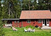 Frau im Liegestuhl vor Ferienhaus (Södermanland, Schweden)