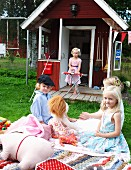 Children playing in front of Wendy house in garden