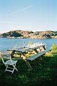 Gedeckter Tisch mit Bänken & Stühlen auf Wiese mit Blick auf See und Berglandschaft