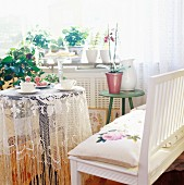 60s-style interior with bench & small table with lace tablecloth below window full of houseplants