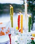 Candles of different colours in glass candlesticks on table in garden