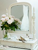 Vase of roses on romantic dressing table with mirror