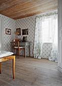 Ahnengalerie an Wand & auf Tisch in Ecke eines Wohnraumes mit Holzdecke & Holzdielenboden
