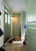 Long hall with wooden floor & mint green doors