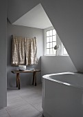 Minimalist bathroom with rustic console table and bathtub under sloping ceiling