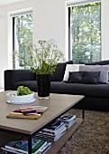 Quadratischer Couchtisch vor schwarzer Couch in Wohnzimmer mit großen Fenstern; auf dem Tisch eine schwarze Vase mit frischen Wiesenblumen