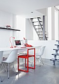 Office in white and red with long desk and white Eames chairs below gallery