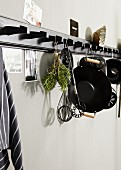 Cooking and baking utensils hanging from black hook rack
