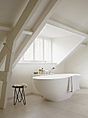 Minimalist bathroom with free-standing bathtub and long dormer window