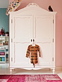 White-painted, antique wardrobe against pink wall in child's bedroom