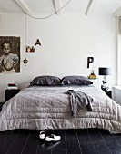 Doppelbett mit großer Steppdecke in Schlafzimmer mit schwarzem Holzdielenboden