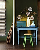 Pastel blue table and stool against olive green wall; collection of china plates on wall