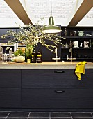 Black kitchen counter with stone top below glass ceiling; bouquet of olive branches on worksurface