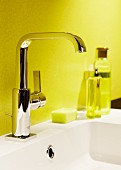 Shiny washbasin tap fittings against yellow bathroom wall