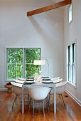White shell chairs at set table between windows in minimalist dining room