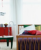 Wooden bed, scatter cushions & small bedside table on flokati rug in bedroom