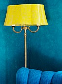 Antique, yellow standard lamp against blue living room wall