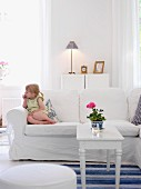 Little girl sitting on sofa in living room