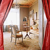 View through open door with curtains into elegant interior with carpet, antique seating & chandelier