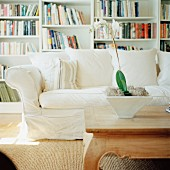 White sofa & wooden coffee table in front of bookshelves on wall