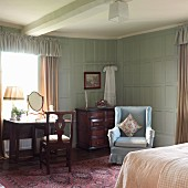 Old-fashioned bedroom with wingback chair and pastel blue wall panelling