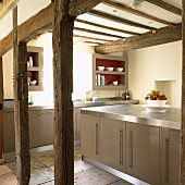 Modern fitted kitchen with island counter in old, half-timbered house with exposed beam structure