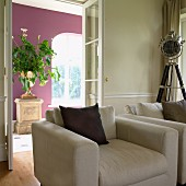 Two armchairs in interior; urn of flowers on stone pedestal against deep violet wall in background
